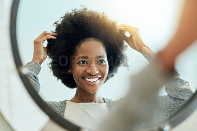 Buy stock photo Shot of an attractive young woman admiring herself in a bathroom mirror at home