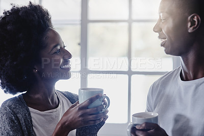 Buy stock photo Shot of a happy young couple enjoying their morning coffee together at home