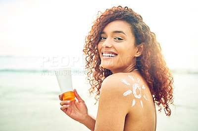 Buy stock photo Cropped portrait of an attractive young woman applying sunscreen at the beach