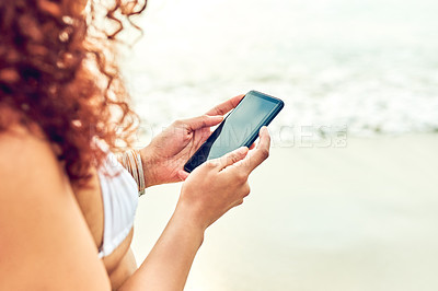 Buy stock photo Cropped shot of an unrecognizable young woman sending text messages while standing on the beach