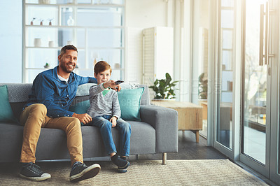 Buy stock photo Shot of a cheerful little boy and his father watching television together while being seated on the sofa at home