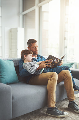 Buy stock photo Shot of a carefree little boy and his father relaxing on a sofa while reading a book at home during the day