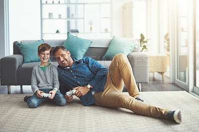 Buy stock photo Shot of a cheerful little boy and his father playing video games together on the television while being seated on the floor at home during the day