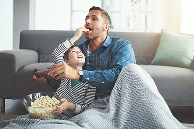 Buy stock photo Shot of a carefree young boy and his father watching a movie together while being seated on the floor and eating popcorn at home during the day