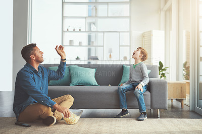 Buy stock photo Shot of a carefree little boy and his father playing around in the living room at home during the day