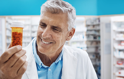 Buy stock photo Cropped shot of a pharmacist holding up capsules