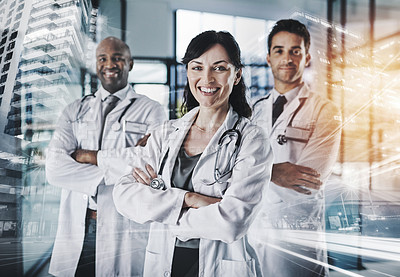 Buy stock photo Cropped portrait of a team of confident doctors standing with their arms crossed in a hospital