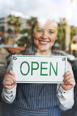Buy stock photo Portrait of a young woman holding up an open sign in her store