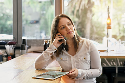 Buy stock photo Shot of a young entrepreneur talking on the phone while using a digital tablet in her cafe