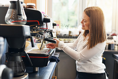 Buy stock photo Shot of a young woman preparing fresh coffee in a cafe
