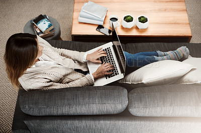 Buy stock photo Shot of an attractive young woman sitting on her sofa while working at home on her laptop