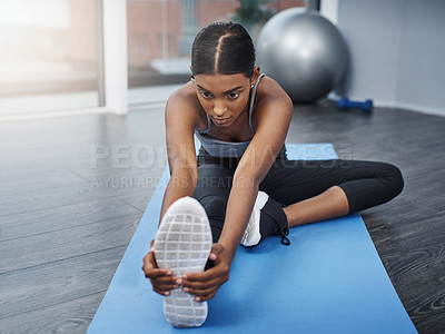 Buy stock photo Shot of an attractive young woman sitting down and doing stretching exercises on her gym mat at home