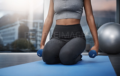 Buy stock photo Cropped shot of an unrecognizable young woman on her knees holding dumbbells while exercising on her gym mat at home