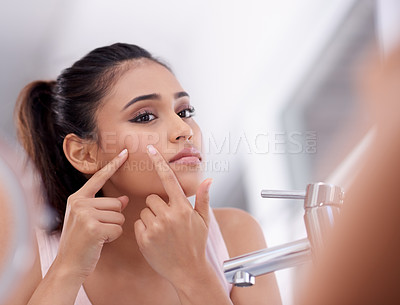 Buy stock photo Shot of a young woman squeezing a pimple on her face in the bathroom