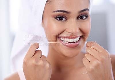 Buy stock photo Portrait of a young woman flossing her teeth in the bathroom