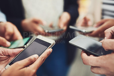 Buy stock photo Shot of a group of unrecognizable businesspeople browsing on their cellphones while standing in a circle at work during the day