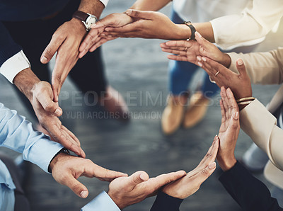 Buy stock photo Closeup of a group of unrecognizable businesspeople holding hands in a certain way to form a circle inside of the office