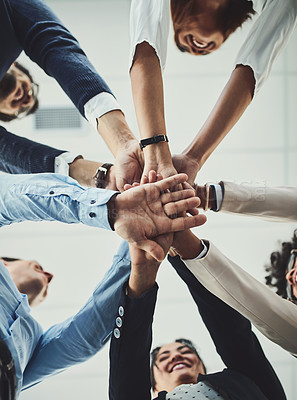 Buy stock photo Low angle shot of a group of businesspeople forming a huddle with their hands inside of the office during the day