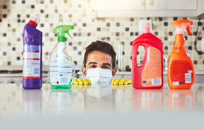 Buy stock photo Cropped portrait of a handsome young man peaking over the kitchen counter while cleaning his home