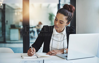 Buy stock photo Shot of a young businesswoman making notes at her desk in a modern office