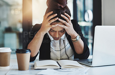 Buy stock photo Shot of a young businesswoman looking stressed while working at her desk in a modern office