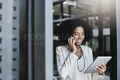 Buy stock photo Shot of a young businesswoman talking on a cellphone while holding a digital tablet in her office