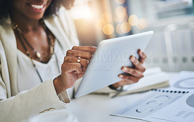 Buy stock photo Shot of an unrecognizable businesswoman using her digital tablet at her office desk