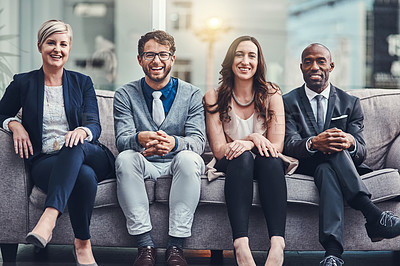 Buy stock photo Cropped portrait of a group of businesspeople sitting on a couch in an office