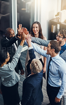 Buy stock photo High angle shot of a group of businesspeople high fiving in an office