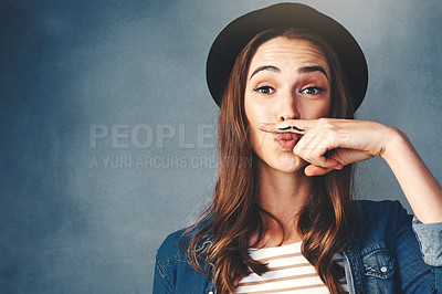 Buy stock photo Studio shot of an attractive young woman making a finger moustache against a blue background