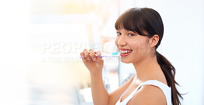 Buy stock photo Portrait of a cheerful attractive young woman brushing her teeth at home during the day