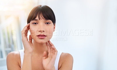 Buy stock photo Portrait of a cheerful attractive young woman touching her face while looking into a mirror at home during the day
