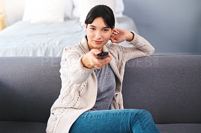 Buy stock photo Portrait of a cheerful young woman holding a remote to change channels while watching television at home