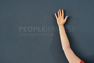 Buy stock photo Studio shot of an unrecognizable person raising their hand against a grey background