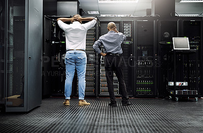 Buy stock photo Rearview shot of two IT technicians having difficulty repairing a computer in a server room