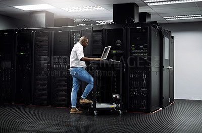 Buy stock photo Full length shot of an IT technician using a computer while working in the server room of a data center