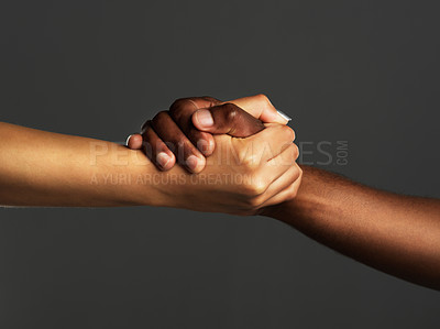 Buy stock photo Studio shot of two unrecognizable people holding hands against a grey background
