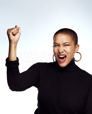 Buy stock photo Studio shot of an attractive young woman posing with her arm raised and fist clinched against a grey background