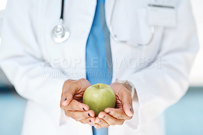 Buy stock photo Cropped shot of a doctor holding a green apple in a hospital