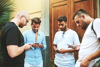 Buy stock photo Shot of a group of friends using their smartphones together in the city
