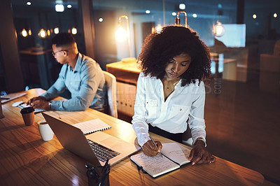 Buy stock photo Shot of a young businesswoman writing notes while working alongside her colleague in an office at night