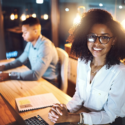 Buy stock photo Portrait of a young businesswoman working alongside her colleague in an office at night