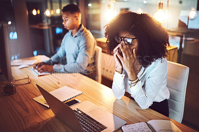 Buy stock photo Shot of a young businesswoman rubbing her eyes while working alongside her colleague in an office at night