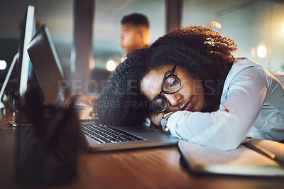 Buy stock photo Shot of a young businesswoman sleeping on her desk in an office at night