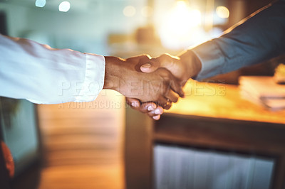 Buy stock photo Closeup shot of two unrecognizable businesspeople shaking hands in an office at night