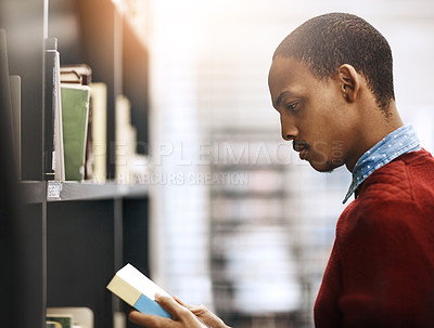 Buy stock photo Shot of a university student looking for a book in the library at campus