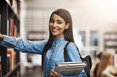 Buy stock photo Portrait of a university student browsing for books in the library at campus