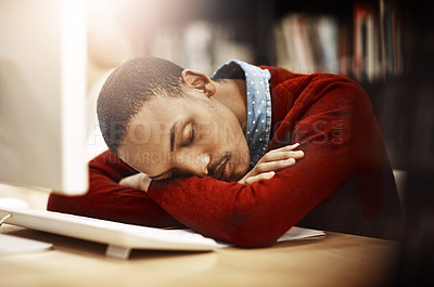 Buy stock photo Shot of a university student sleeping while working on a computer in the library on campus