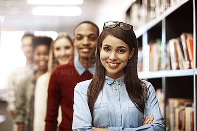 Buy stock photo Portrait of a group of university students standing together in the library on campus