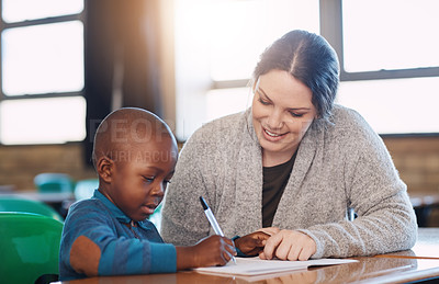 Buy stock photo Cropped shot of an elementary school boy and his teacher doing school work together in the classroom